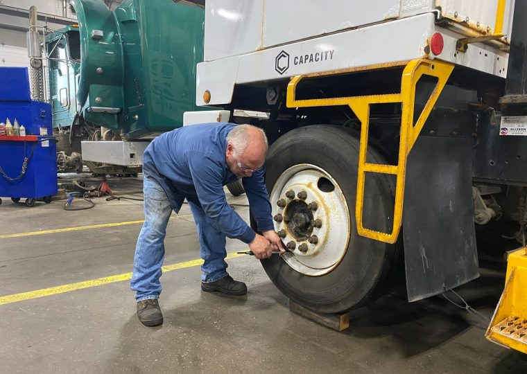 checking air pressure in semi truck tires for preventative maintenance - Blaine Bros.